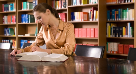 Woman Studying At Desk In Library