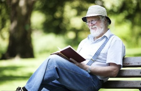 Elderly man with beard and hat reading in a park